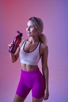 젊은 섹시한 운동가는 스튜디오, 네온 배경에서 물을 마신다. 사진 촬영에서 피트니스 여성, 스포츠 컨셉, 활동적인 라이프 스타일 동기 부여