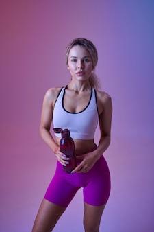 젊은 섹시한 운동가는 스튜디오, 네온 배경에서 물을 마신다. 사진 촬영, 스포츠 컨셉, 활동적인 라이프 스타일에서 피트니스 여성