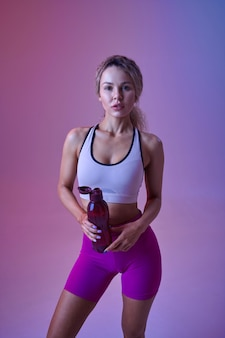 Young sexy sportswoman drinks water in studio, neon background. fitness woman at the photo shoot, sport concept, active lifestyle