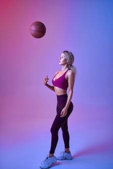 Young sexy sportswoman with ball poses in studio, neon background. fitness woman at the photo shoot, sport concept, active lifestyle motivation