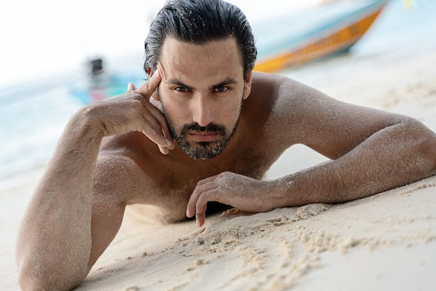 Young sexy stylish handsome latin man lies on a tropical beach, sand on tanned skin, sunbathing vacation concept.