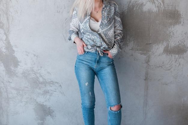 찢어진 세련된 청바지에 여름 유행 셔츠에 젊은 섹시 세련된 여자는 회색 콘크리트 벽 근처에 서있다