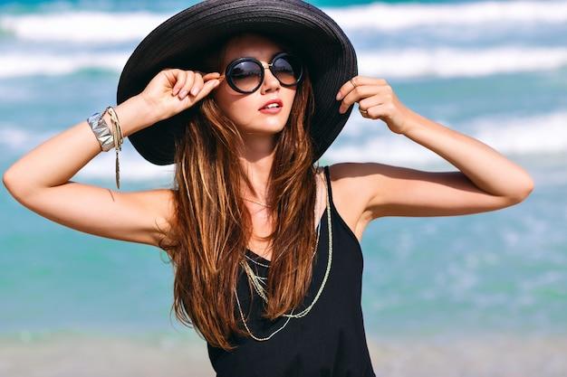 Giovane donna alla moda sexy che indossa un look total back, goditi la sua vacanza di lusso su un'isola esotica, camminando vicino all'oceano blu, indossando cappello e occhiali da sole alla moda