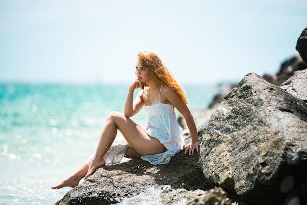 Молодая сексуальная женщина на море, летний пляж, чувственная девушка, девушка в белом платье на тропическом пляже