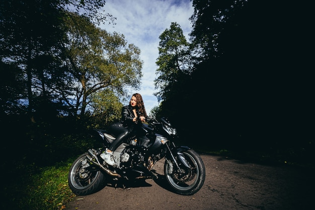 Young sexy woman in a black leather jacket sitting on a black sports motorcycle on the background of a beautiful forest road