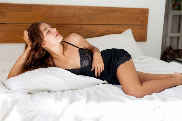Young sexy woman in black lingerie posing in bed