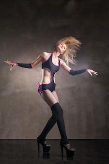 灰色の背景の上にスタジオで踊る若いセクシーな女性