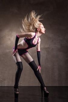 회색 배경 위에 스튜디오에서 춤을 추는 젊은 섹시한 여자