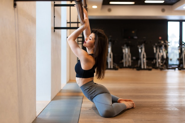 Young sexy woman doing stretching exercises in gym