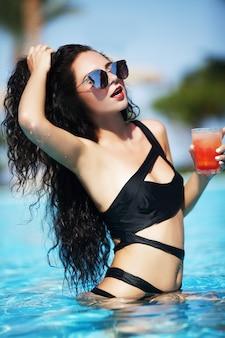 屋外スイミングプールの端で休息を楽しんでいる若いセクシーな女性