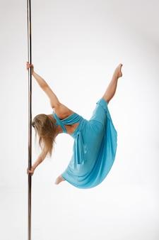 Молодая сексуальная женщина упражнения полюс танец на сером фоне