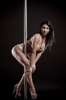 Giovane donna sexy esercizio pole dance contro uno sfondo nero