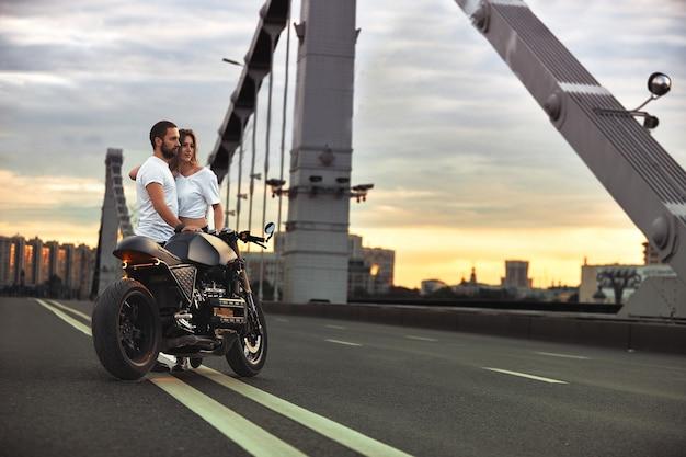 Молодая сексуальная женщина обнимает симпатичного мужчину в стильной черной кожаной куртке, сидит на спортивном мотоцикле на мосту в городе на закате и целуется