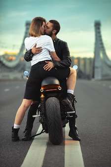 세련 된 블랙 가죽 자 켓에 귀여운 남자를 포옹, 일몰에 도시의 다리에 스포츠 오토바이에 앉아 키스 젊은 섹시 한 여자.
