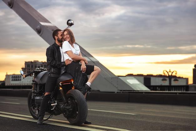スタイリッシュな黒い革のジャケットでかわいい男を抱き締め、日没時に街の橋の上のスポーツバイクに座ってキスをしている若いセクシーな女性。