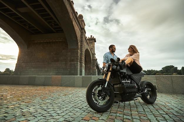 Молодая сексуальная женщина обнимает симпатичного мужчину в стильной черной кожаной куртке, сидит на спортивном мотоцикле под мостом в городе на закате и целуется.