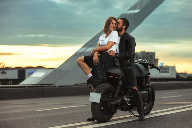 Young sexy woman hugging cute man in stylish black leather jacket, sitting on sports motorcycle on the bridge in the city on sunset and kissing.