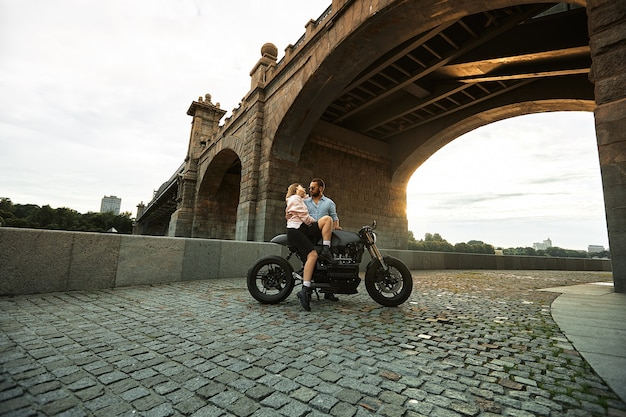 Young sexy woman hugging cute man in stylish black leather jacket, sitting on sports motorcycle under the bridge