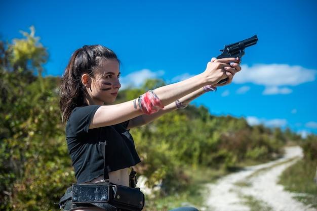자연에서 총을 들고 위쪽과 반바지를 입고 젊은 섹시 한 여자 사냥꾼