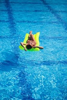 水着姿の若いセクシーな女性は、膨脹可能なマットレスの上でプールで泳ぎます。休暇中の青いプールでサングラスをかけた女の子