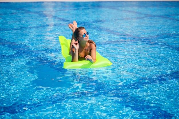 Молодая сексуальная женщина в купальнике плавает в бассейне на надувном матрасе. девушка в солнечных очках в синем бассейне на отдыхе