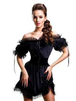 Молодая сексуальная женщина в черном платье позирует на белой стене