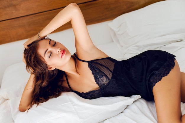 ベッドでポーズをとって黒いランジェリーの若いセクシーな女性