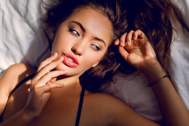 Молодая сексуальная женщина в черном белье позирует в постели