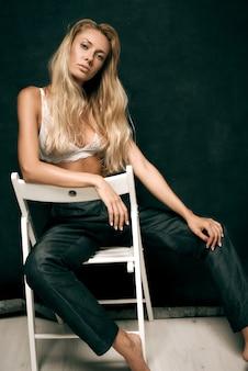 브래지어에 젊은 섹시 한 여자는 어두운 배경에 의자에 앉아