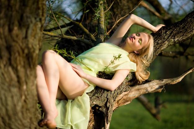 緑の自然と夏の日の水の上の木の幹に座っている緑のドレスの若いセクシーな女性