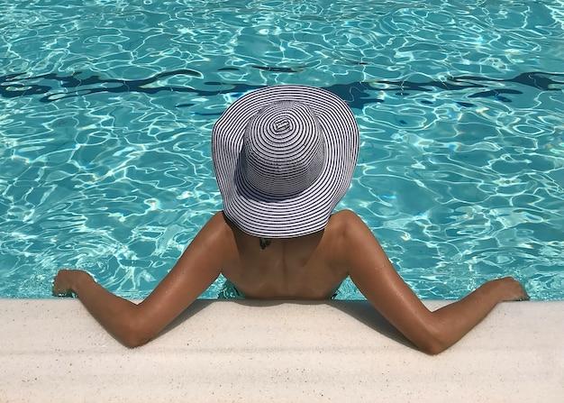 Молодая сексуальная женщина в шляпе, расслабляющаяся у бассейна