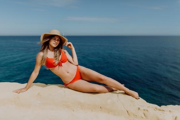 海と岩の端に横たわって赤いビキニと麦わら帽子の若いセクシーな女性