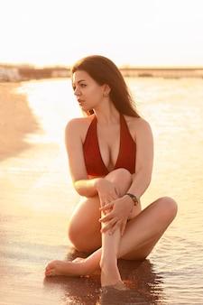 Молодая сексуальная женщина в красном купальнике бикини, сидя на пляже