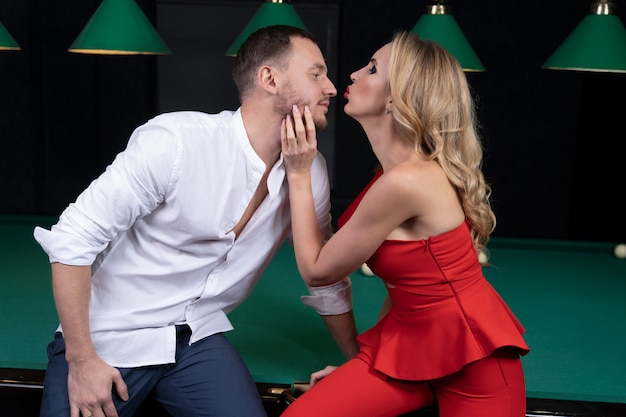 赤い服の若いセクシーな女性は、あごで男を連れて行き、ビリヤード台に座って彼の鼻にキスしたい