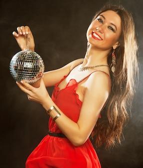 디스코 볼을 유지하는 빨간색 드레스에 젊은 섹시 한 여자