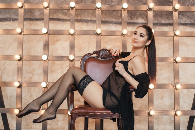 Молодая сексуальная женщина в чулках на стуле