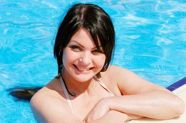 プールの幸せな日の若いセクシーな女性