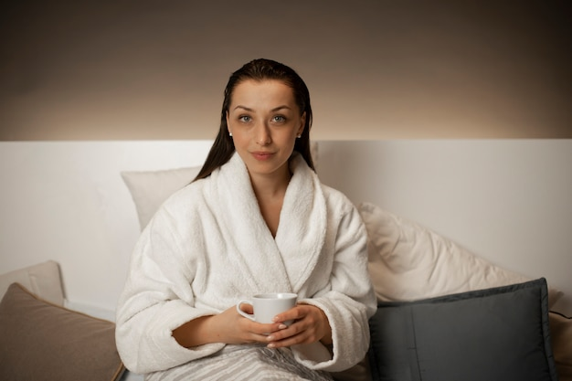 흰 가운에 젊은 섹시한 여자는 침대에 앉아 차를 마시는 동안 휴식