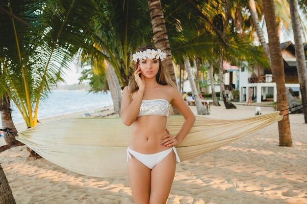 Молодая сексуальная женщина в белом купальнике бикини позирует на тропическом пляже, пальмы, гавайи, цветы в волосах, чувственное, стройное тело, солнечно, наслаждаясь отпуском, путешествуя по острову