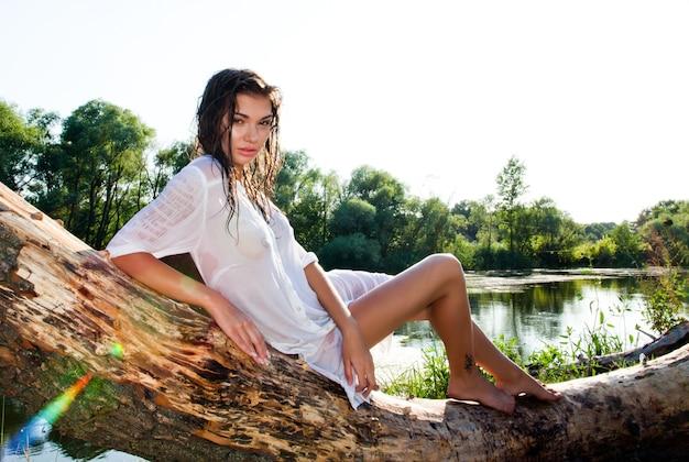 緑の自然と夏の日に水を木の幹の上に横たわる白いドレスの若いセクシーな女性