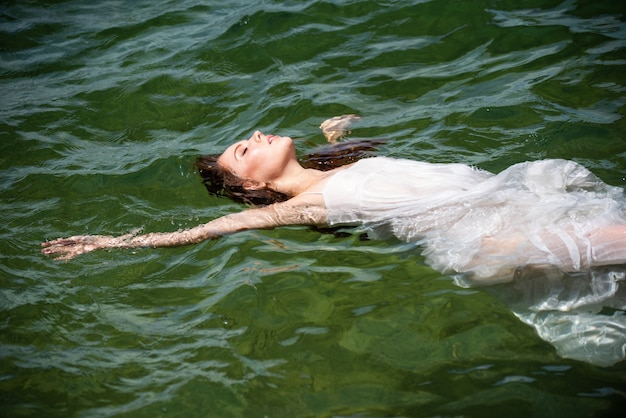 Young sexy woman is swimming in the transparent, blue sea. sensual slim woman floating on the water of ocean water.