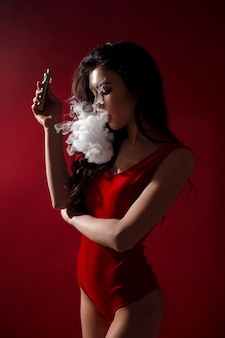 Young sexy woman is vaping. a cloud of vapor.