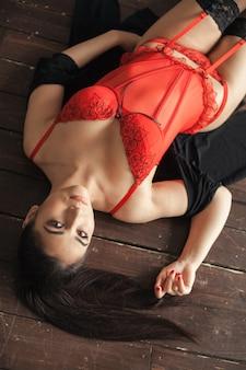 Молодая сексуальная женщина, лежа на деревянном полу