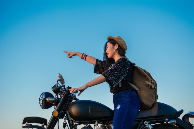Young sexy woman on a motorcycle in nature on the sunset. travel concept.
