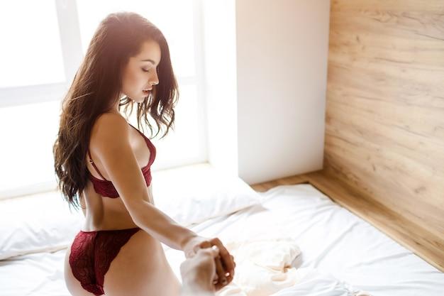 ベッドの上の若いセクシーな女性。カメラに向かってポーズをとって見下ろします。男の手を握ってください。美しい赤いランジェリーを着用してください。ホットセクシーな女性はベッドの上に立っています。明け