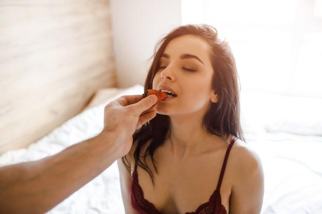 침대에 젊은 섹시 한 여자. 눈을 감고 앉아. 빨간 딸기 조각을 물고. 여자는 란제리에서 아름다운 브래지어를 착용합니다. 남자는 딸기를 손에 잡는다.