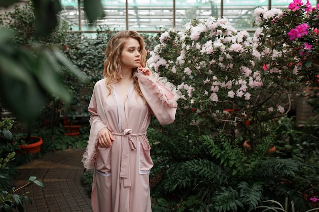 Giovane donna sexy in accappatoio rosa in piedi nel giardino del mattino pieno di fiori