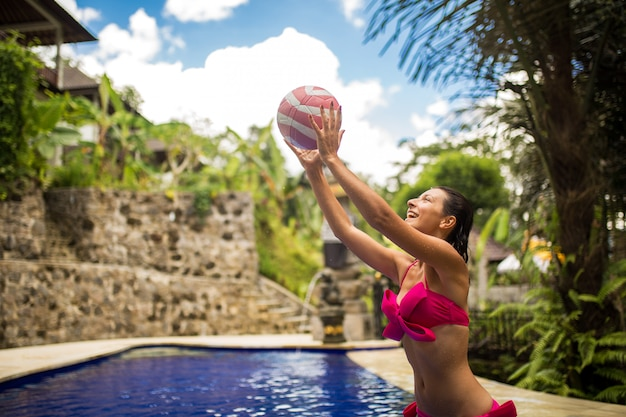Young sexy woman in pink swimsuit plays with ball in tropical swimming pool.