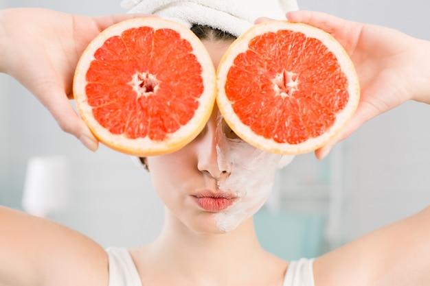 젊은 섹시 한 여자 빛 공간에 그녀의 얼굴에 얼굴과 붉은 자 몽 조각 키스 포즈. 천연 화장품, 스킨 케어, 웰빙, 페이셜 트리트먼트, 미용 개념.