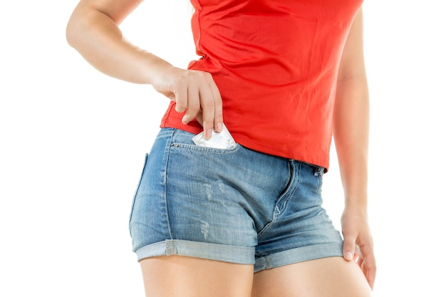 Young sexy woman putting condom in jeans shorts pocket